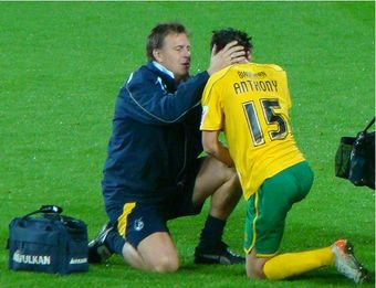 Sports physiotherapist assessing athlete during a match