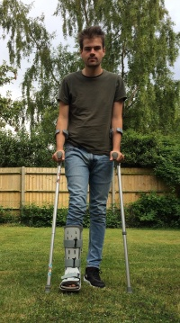 2448px-Teenage boy on crutches with walking boot.jpg